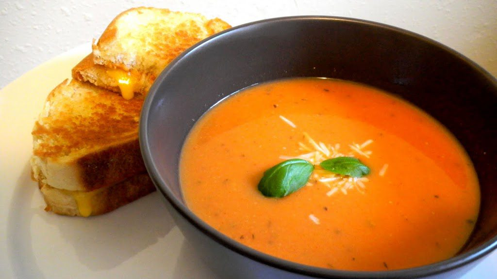 Bowl of tomato soup next to a grilled cheese sandwich