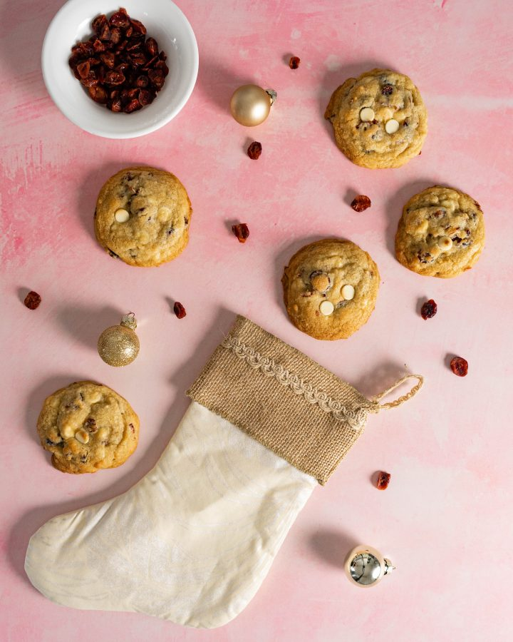 Gold ornaments, cookies, cranberries, and a white stocking on pink background.