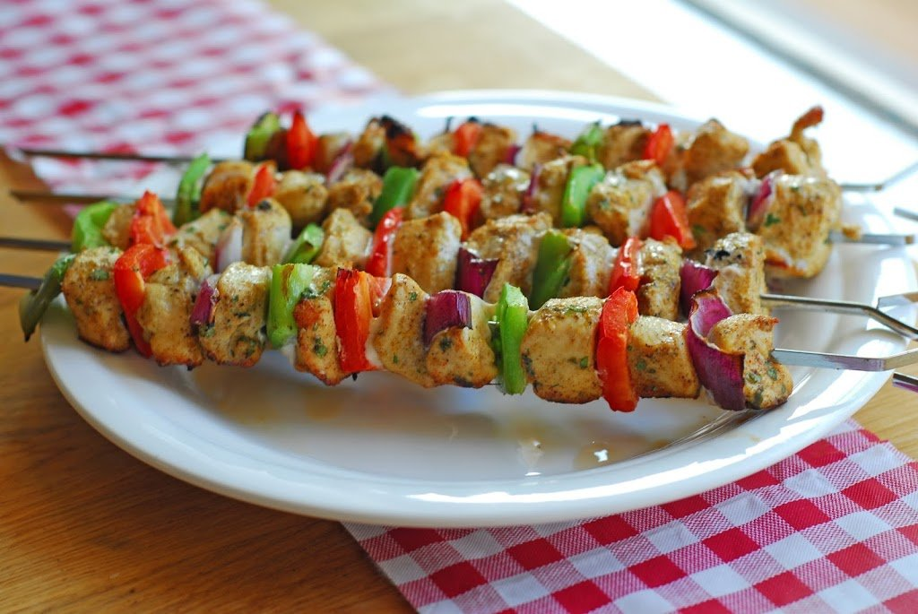 grilled chicken kebabs on a white plate