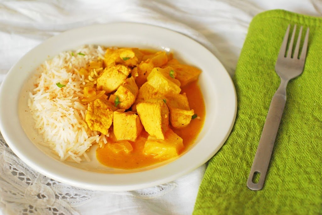 Chicken and pineapple curry and basmati plate on a white plate with green napkin.