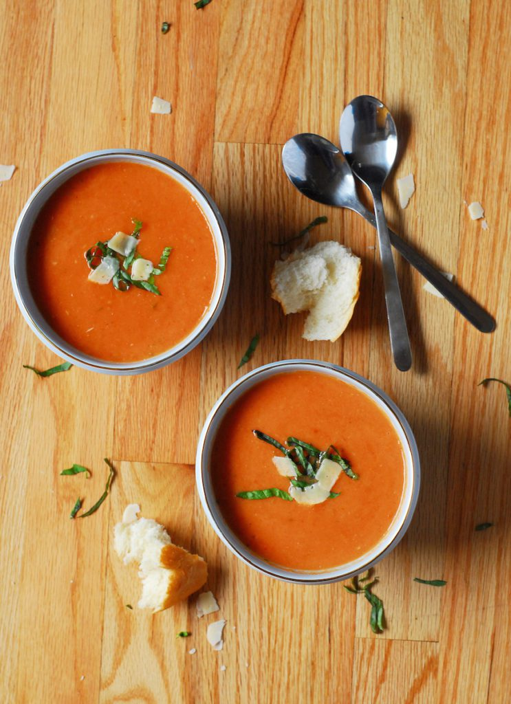 Bowls of tomato soup on wooden surface with hunks of bread and spoons