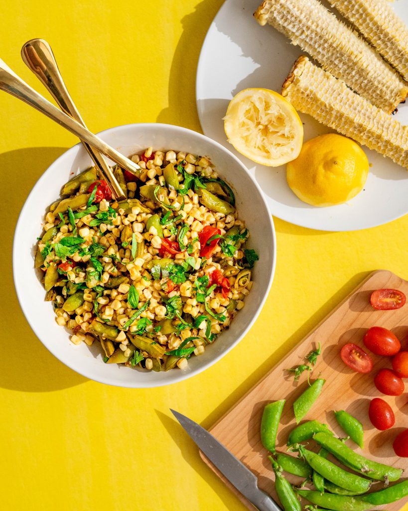 Grilled corn salad in white bowl on yellow surface with ingredients surrounding