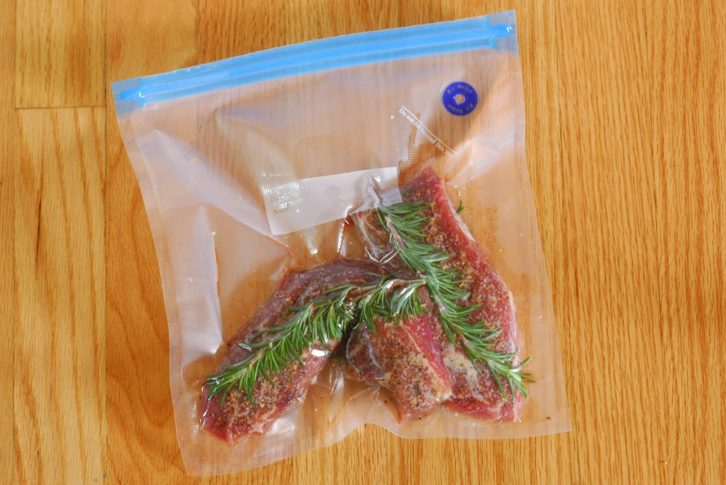 Seasoned steak and rosemary sprigs in reusable sous vide bag on wood surface