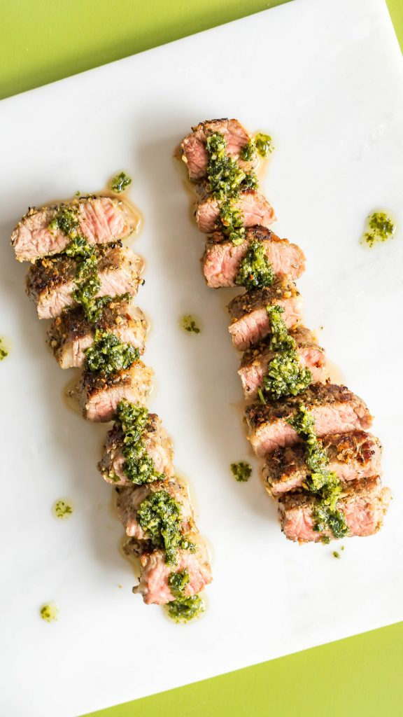 Sliced sous vide steak on a marble slap on a green backdrop with chimichurri sauce spread over