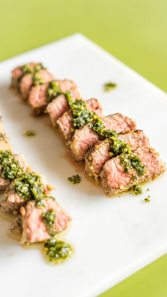 Close up of sliced sous vide steak with chimichurri on marble board on green background