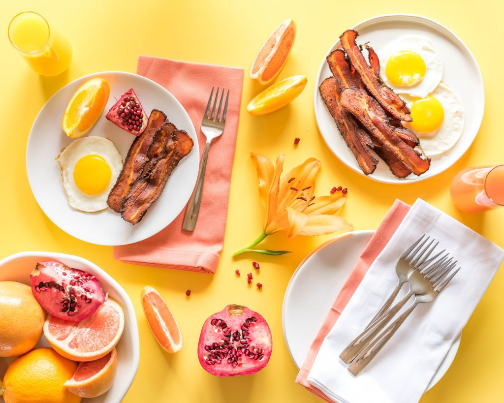 Sous Vide Bacon, eggs, and fruit arranged on white plates and a yellow background