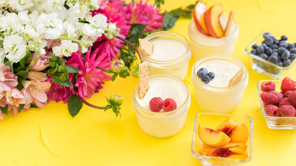 Lemon Cheesecake served in glass jars on a yellow background