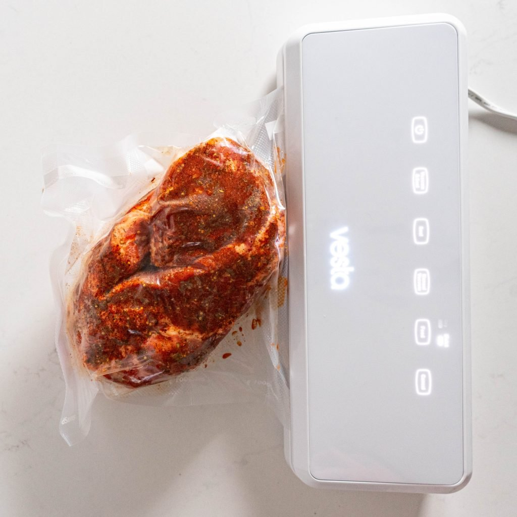 Vacuum sealed pork shoulder on white surface
