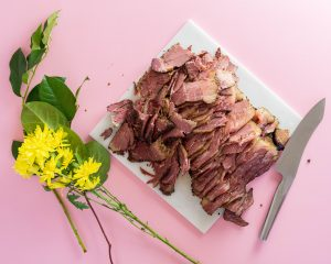 Sliced pastrami on a marble slab with flowers and a pink background.