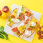 Flatbread with tomatoes and burrata cut into pieces on a marble slab