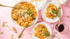 Bowls of pasta arranged on a pink background
