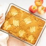 Brown butter apple blondies in glass baking dish being set down on white surface with apples