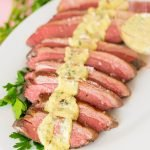 Sliced beef on a platter with parsley and horseradish dijon sauce spooned over the meat.
