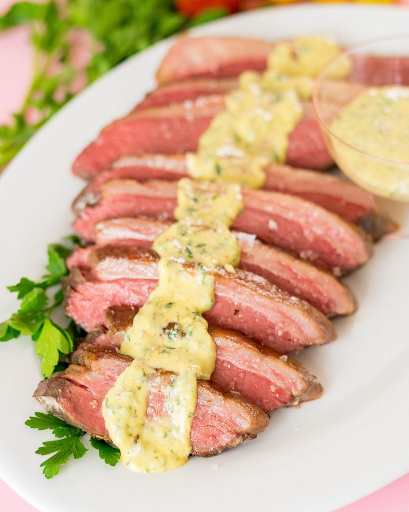 Sliced picanha steak on a platter with parsley and horseradish dijon sauce spooned over the meat.