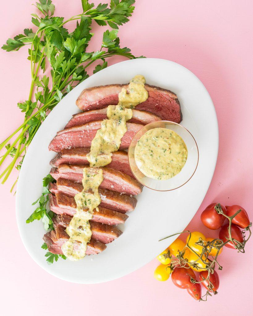 Sliced steak picanha steak with horseradish sauce over it