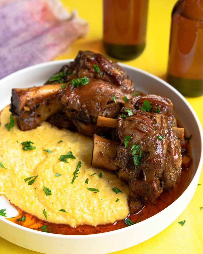 Braised pork shanks over grits on a white platter on a yellow background