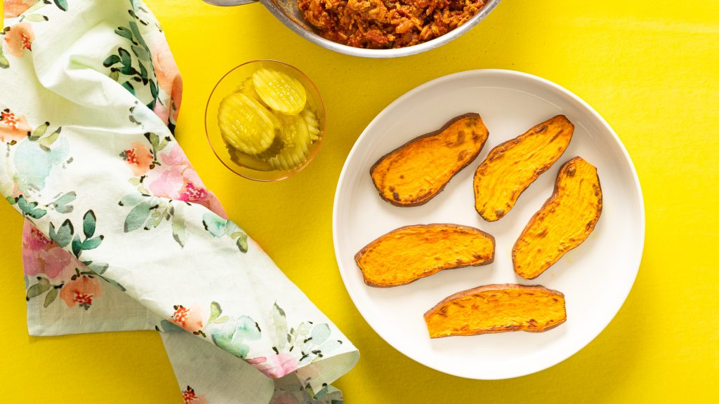 Cooked sliced sweet potatoes on yellow plate on yellow surface