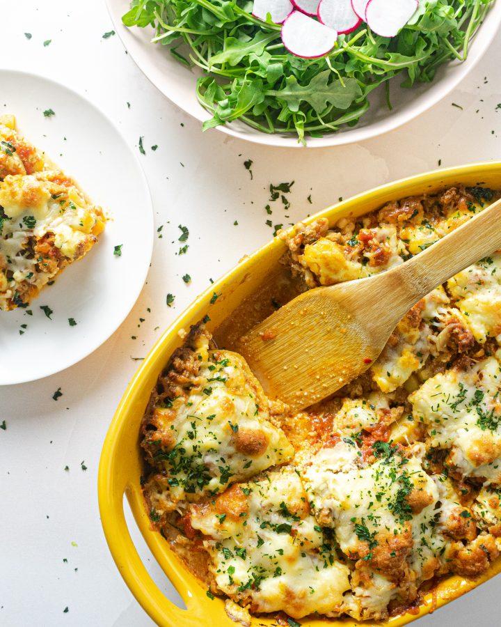 Polenta lasagna in yellow baking dish, white plate with slice of polenta lasagna, green salad in white bowl on pink surface