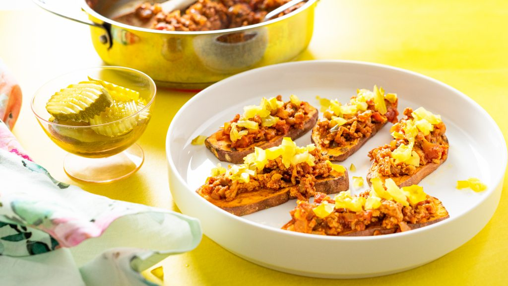 Sloppy Joe Sweet Potato Toasts on a while plate on a yellow background with pickles in a dish