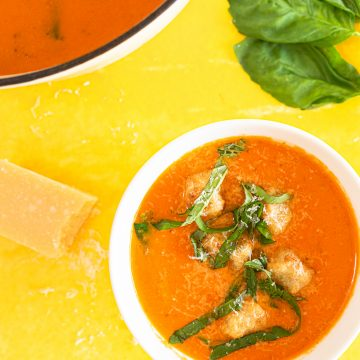 Bowl of tomato soup with cauliflower dumplings on yellow surface