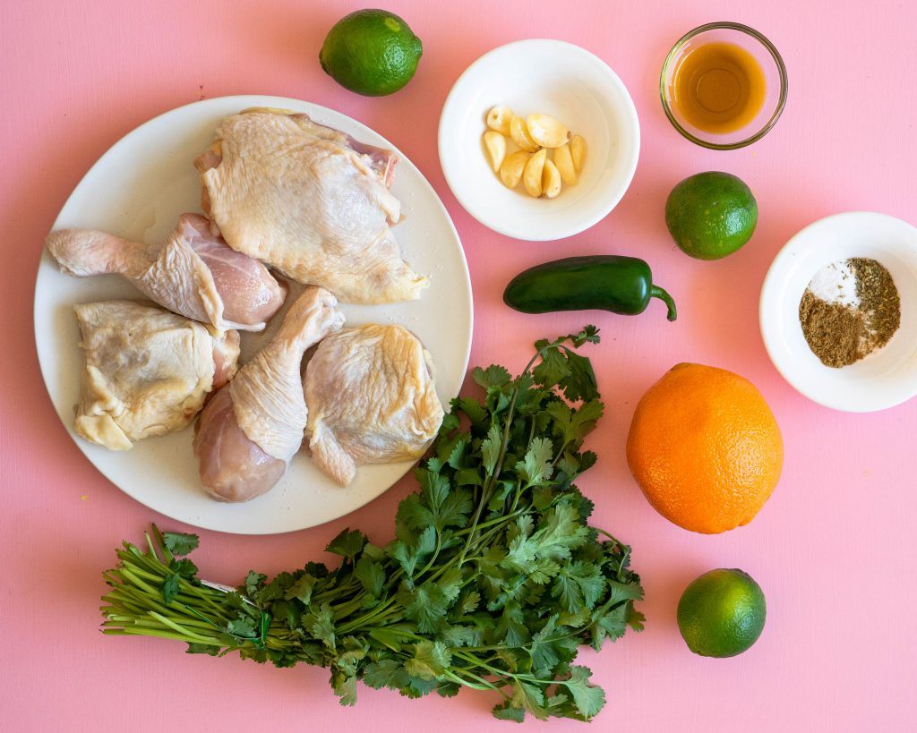 Raw chicken, cilantro, jalapeno, orange, limes, olive oil, and spices on pink background