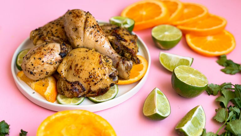 Mojo chicken on a white plate on a pink surface with cut up oranges and limes