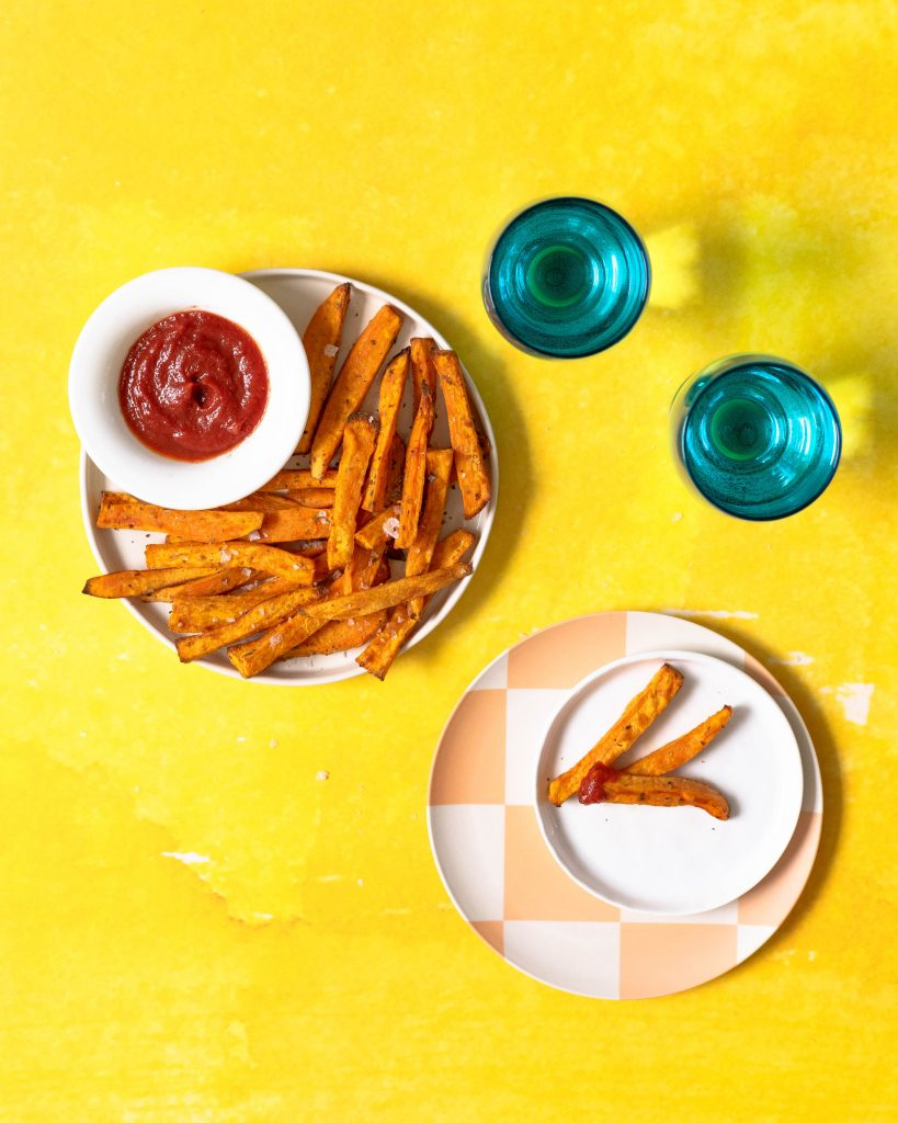 Sweet potato fries on platter with bowl of ketchup on yellow background