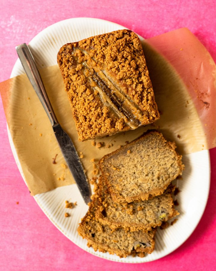 Banana bread on a white platter on a hot pink surface