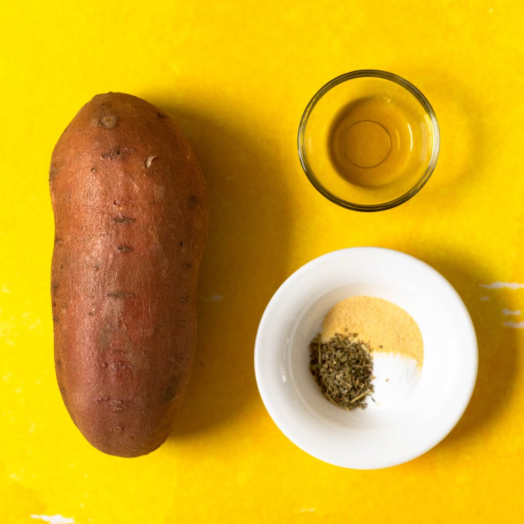 Sweet potato, spices, and olive oil on yellow background
