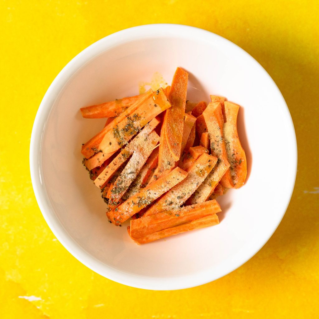 Bowl of slices and seasoned raw sweet potato fries