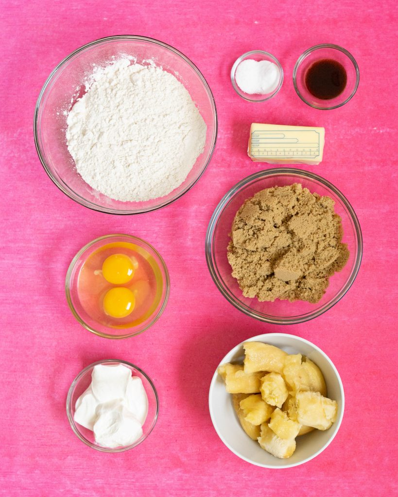 Ingredients for banana bread on pink surface