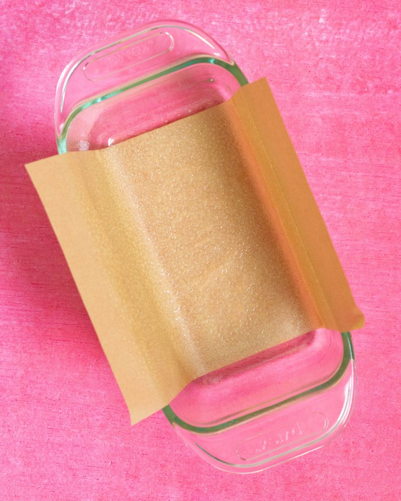 Greased loaf pan with parchment paper on pink surface