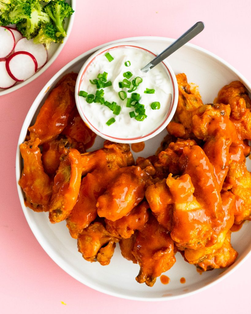 Hot wings on white platter with bowl of blue cheese dip