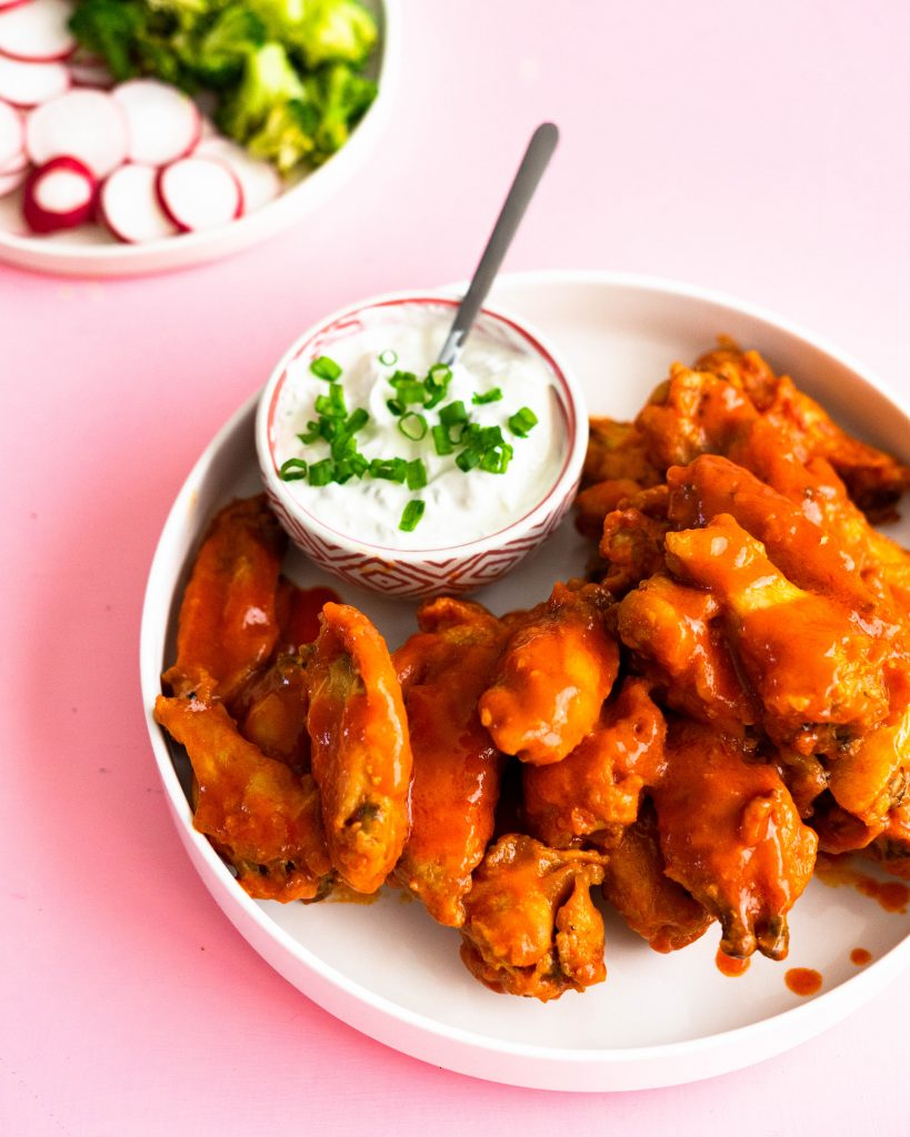 Hot wings on white platter with blue cheese sauce