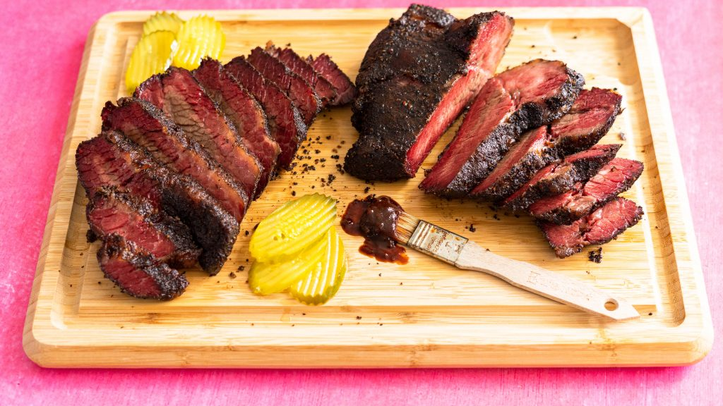 Sliced brisket and pickles on wood cutting board