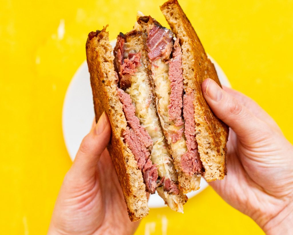 Reuben sandwich over yellow backdrop