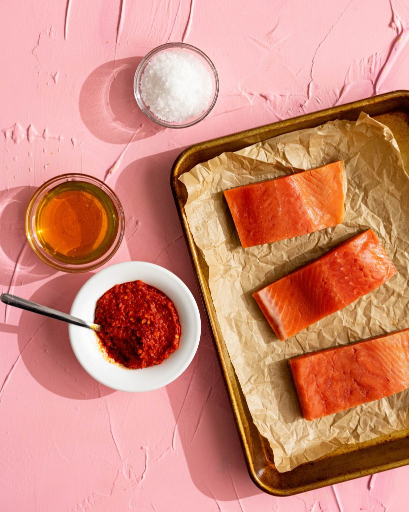 Salmon on parchment paper on baking sheet, bowl of harissa, bowl of honey, bowl of salt