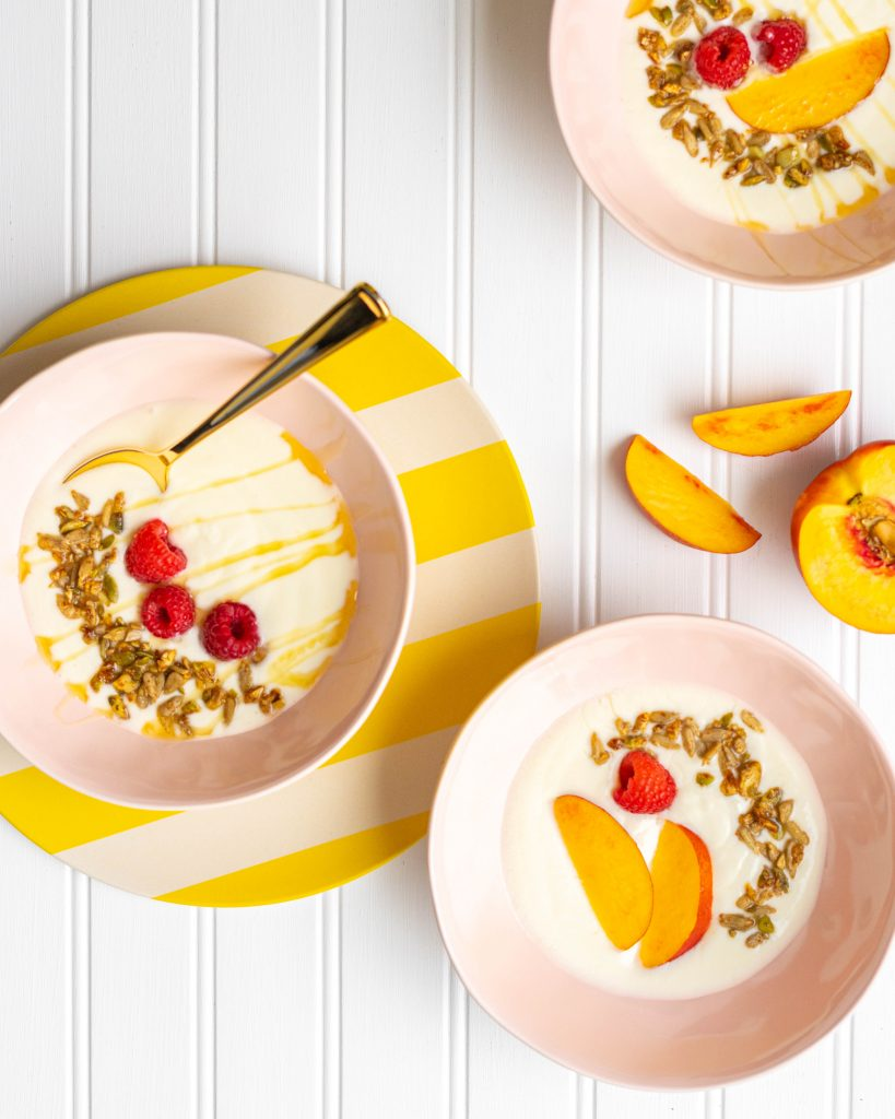 Three pink bowls filled with yogurt and topped with fruit and granola