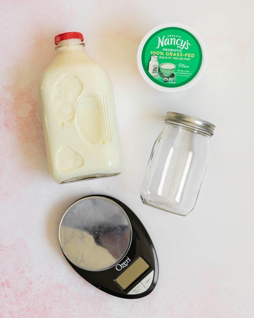 Yogurt, milk, empty glass jar, and food scale