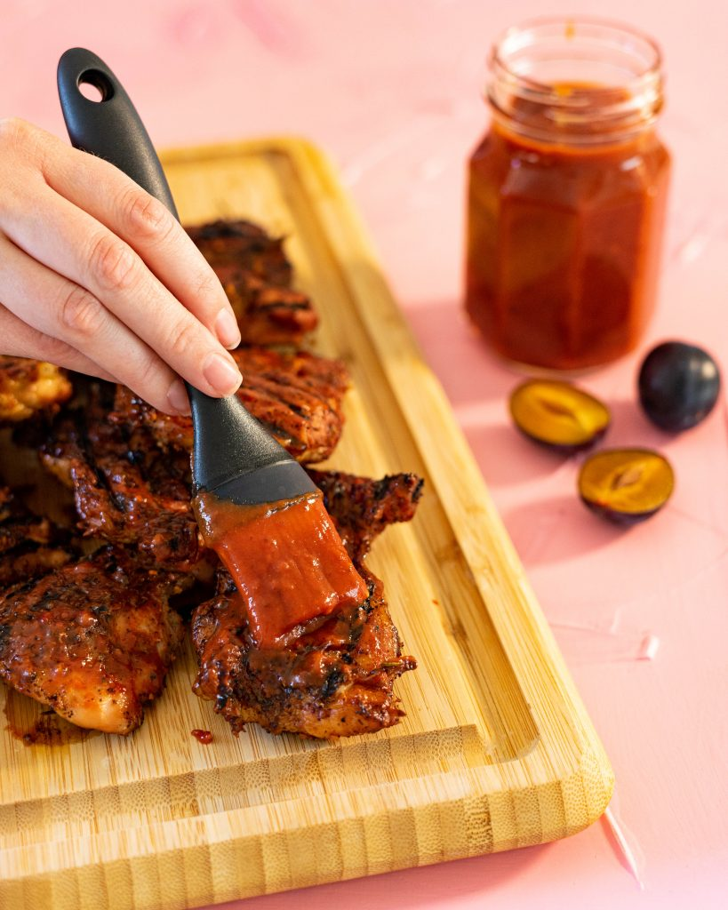 Spreading plum bbq sauce on grilled chicken