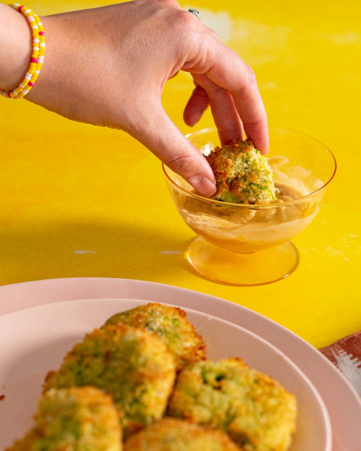 Hand dipping air fried zucchini fritter into dipping sauce with yellow background