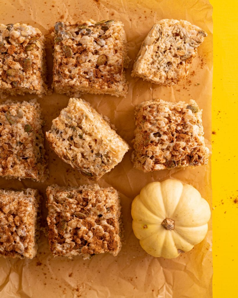 Pumpkin seed rice krispie treats on parchment paper on yellow surface