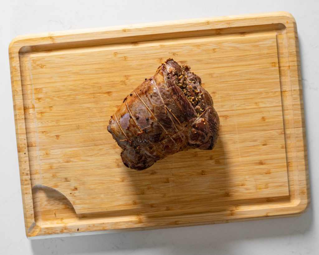 Seared leg of lamb on wood cutting board.