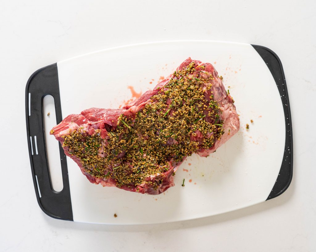 Butterflied leg of lamb spread with rub on cutting board.