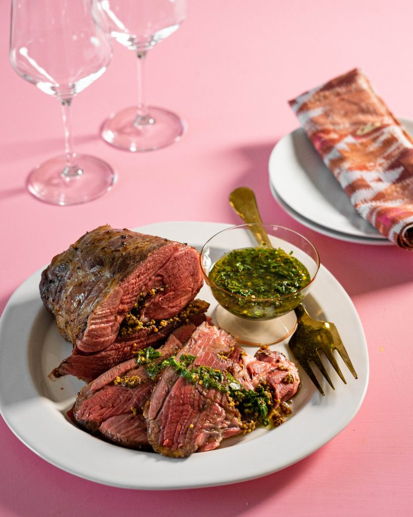 Leg of lamb on serving platter and sliced with salsa verde on pink background.