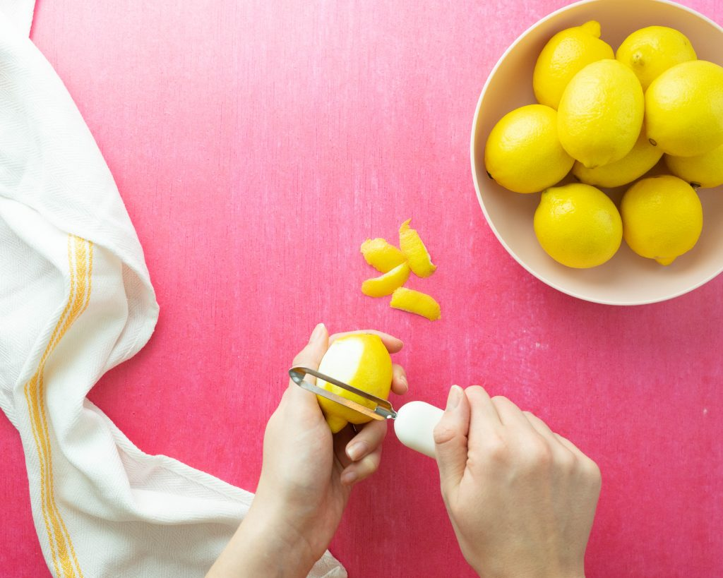 Peeling lemon rind on pink surface