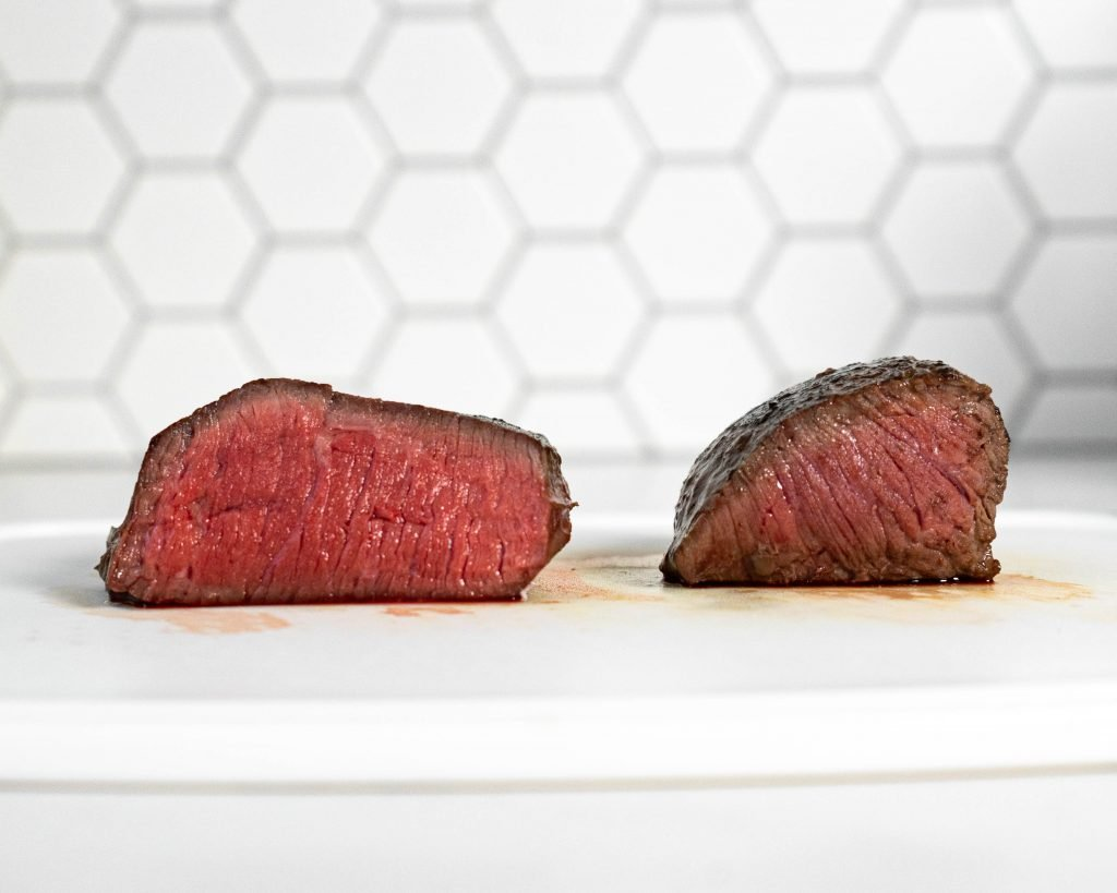 Photo comparing a sous vide steak and a pan seared steak