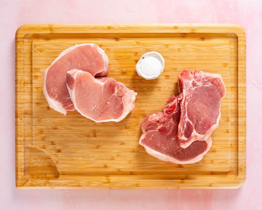 Boneless and bone-in pork chops on wood cutting board