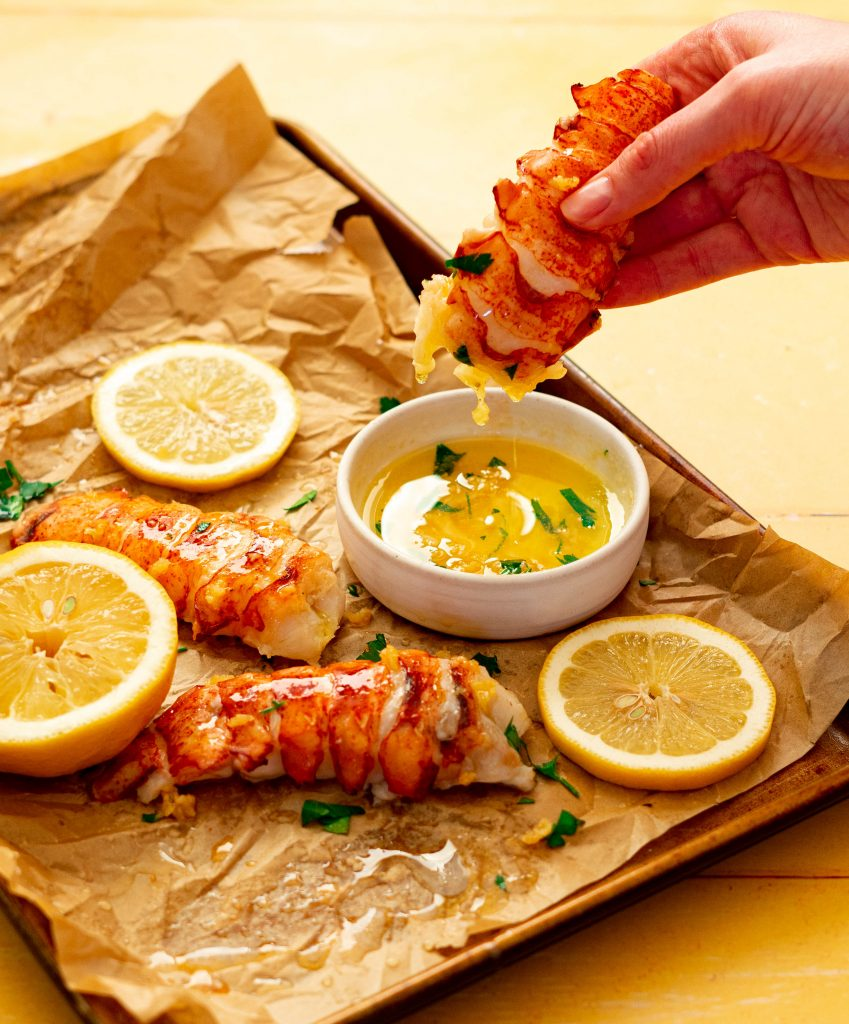 Dipping lobster tail into garlic butter sauce