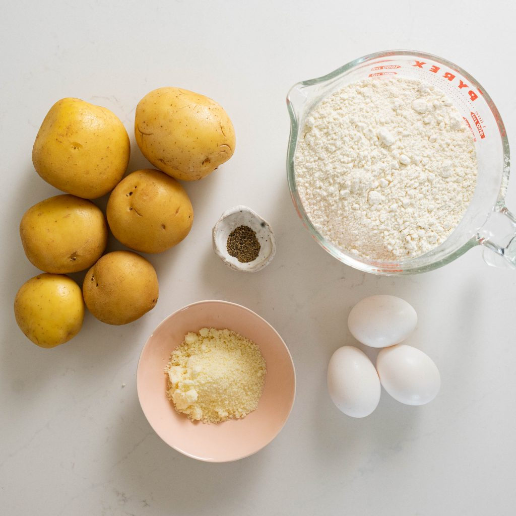 Ingredients for cacio e pepe on white surface